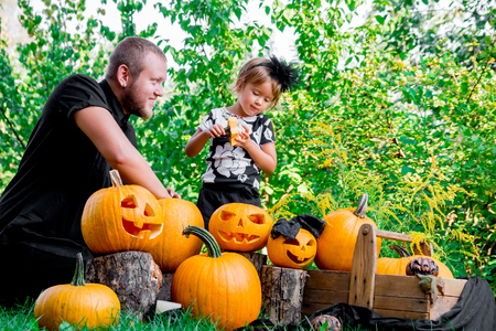 Daughter near father who pulls seeds and fibrous material from a pumpkin before carving for Halloween. Prepares a jack-o-lantern. Decoration for party. Happy family. Little helper. Stock Photo