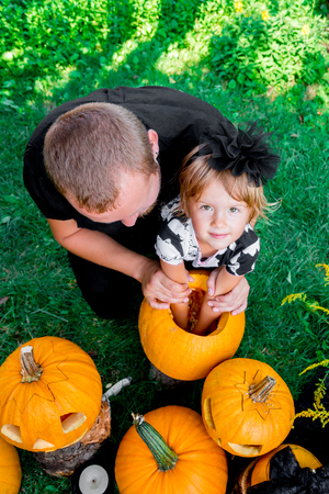 Daughter and father pulls seeds and fibrous material from a pumpkin before carving for Halloween. Prepares a jack-o-lantern. Decoration for party. Happy family. Little helper. Top view.