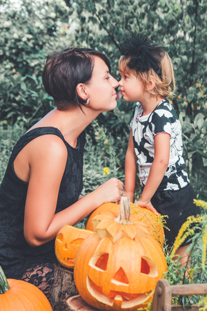 Halloween. Daughter and mother kisses near jack-o-lantern in the garden. Decoration for party. Family.
