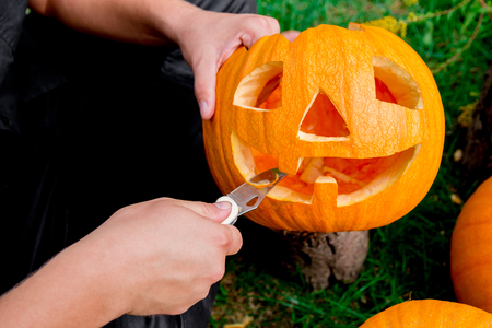A close up of man's hand who cuts with knife a pumpkin as he prepares a jack-o-lantern. Halloween. Decoration for party.