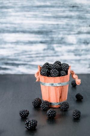black raspberries: Black raspberries in a wooden basket on black wooden background.