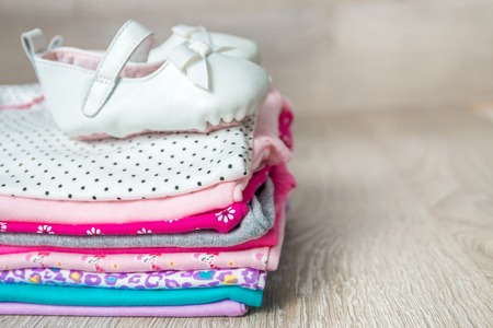baby stuff: Folded pink and white bodysuit with shoes on it on grey wooden background. diaper for newborn girl. Stack of infant clothing. Child outfit. Copy space.