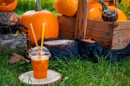 terrifying: Halloween cocktail with pumpkins decoration on background. Punch for a party.