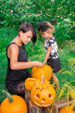 Daughter and mother pulls seeds and fibrous material from a pumpkin before carving for Halloween. Prepares a jack-o-lantern. Decoration for party. Happy family. Little helper.