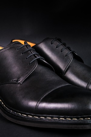 brogue: Black oxford shoes on black background. Back view. Close up.