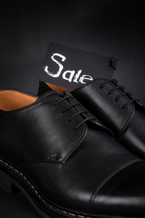 brogues: Black oxford shoes on black background. Back view. Close up.
