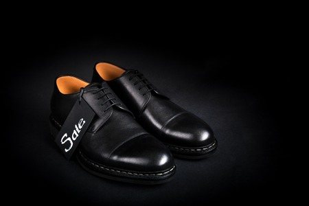 brogues: Black oxford shoes on black background. Back view. Copy space.
