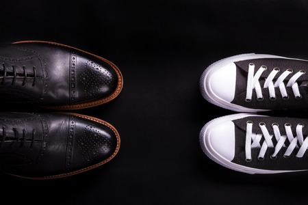 brogue: Mixed shoes. Oxford and sneakers shoe on black background.  Different style of men fashion. Compare of formal and casual. Top view. Copy space.