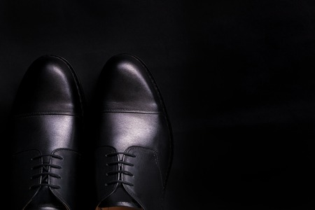 brogues: Black oxford shoes on black background. Top view. Copy space.