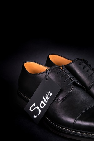 brogue: Sale sign. Black oxford shoes on black background. Back view. Copy space. Close up.