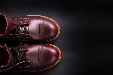 brogues: Fashionable mens leather brown shoes on black background. . Mens high boots. Top view.