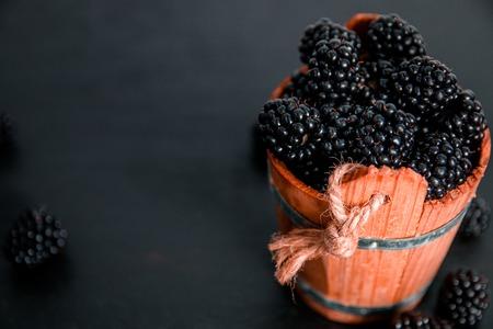 black raspberries: Black raspberries in a wooden basket on black wooden background. Frame. Copy space. Top view.