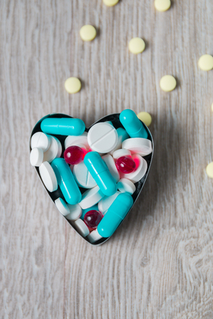 generic drugs: Heart from colorful medication and pills from above on grey wooden background. Copy space. Top view, frame. Painkillers, tablets, generic pills, drugs.