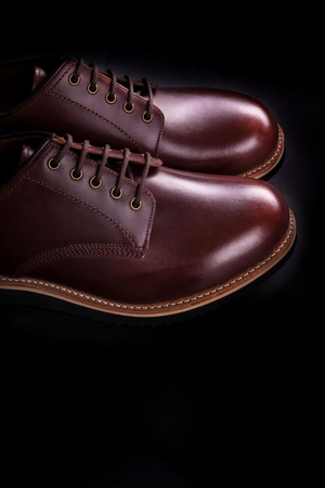 brogue: Brown oxford shoes on black background. Back view. Stock Photo