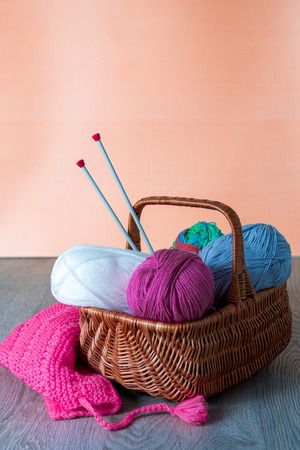 Ball of yarn and knitting needles in basket on a wooden grey table. Handmade. Stock Photo