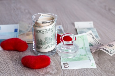 saving tips: Money near red hearts. Dollars in open jar with euro on grey wooden Copy space. Love. Valentine day.