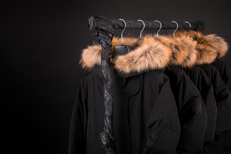 Black coats, jacket with fur on hood hanging on clothes rack. Black background. Copy space.