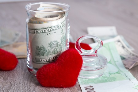 Money and red hearts. Dollars in open jar on grey wooden background. Love. Valentine day. Stock Photo