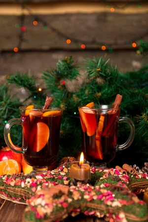 apple cinnamon: Christmas mulled wine with fruits and spices on wooden table. Xmas decorations in background. Two glasses. Winter warming drink with recipe ingredients around. Stock Photo
