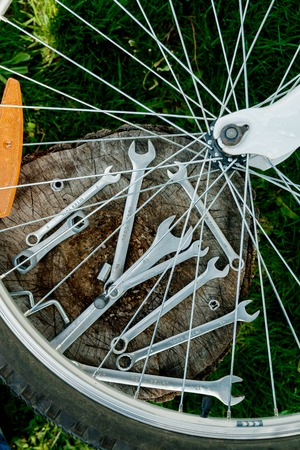 spokes: Bicycle repair. Tools, instrument for repairing bike on the wooden stump background with spokes of a wheel in the foreground.