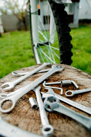 spokes: Bicycle repair. Tools, instrument for repairing bike on the wooden stump background near spokes of a wheel