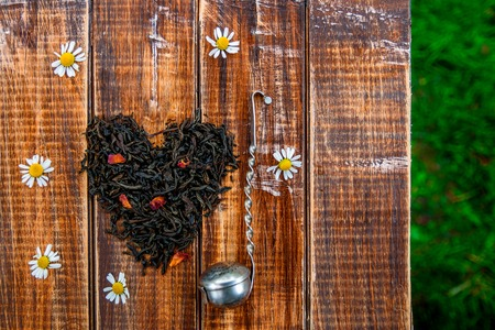 loose leaf: Vintage strainer near dry leaves of black tea make in heart on wooden table in garden and on nature background. Tea concept. Tea leaves. Top view. Closeup. Love. Copy space. Stock Photo
