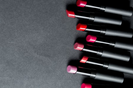 Set of matte Lipstick in red and natural colors on black background. Fashion colorful lipsticks. Professional makeup and beauty. Frame. Top view. Copy space. Stock Photo