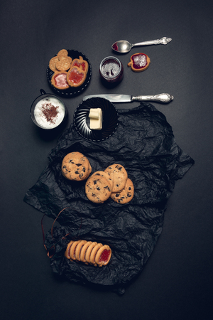 tarde de cafe: Cup of coffee, cappuccino with chocolate cookies and biscuits on black table background. Afternoon break time.