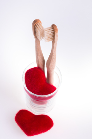 Two beige dental brushes in glass cup with red hearts white background. Isolated. Toned photo. Love. Valentine day. Stock Photo