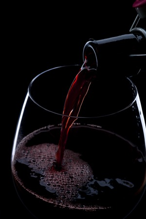 Red wine pouring into a wineglass. Isolated on black