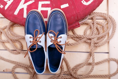Blue boat shoes on wooden background near lifebuoy and rope.