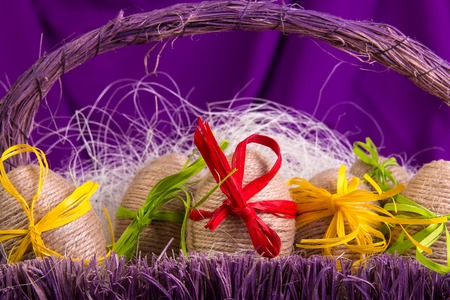 Easter egg decorative in twine in purple basket on wooden table on purple