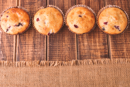 blueberry muffin: Muffins on wooden background on rustic style. Cupcake with currant. Copy space. Top view.