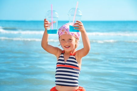 swimsuite: Happy little girl in  swimsuit with two blue cocktail on the beach. Summer. Vacation. Sea. Ocean.