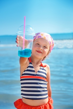 swimsuite: Happy little girl in  swimsuit with blue cocktail on the beach. Summer. Vacation. Sea. Ocean.