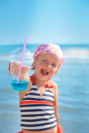 swimsuite: Happy little girl in  swimsuit with blue cocktail on the beach. Summer. Vacation. Sea. Ocean Stock Photo