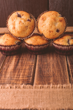 blueberry muffin: Muffins on wooden background on rustic style. Cupcake with currant. Copy space