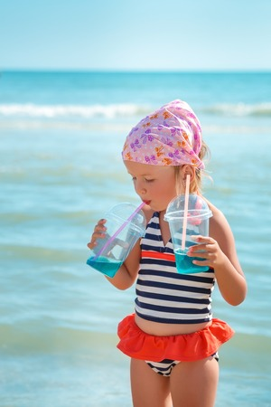 swimsuite: Happy little girl in swimsuit drink cocktail on the beach. Summer. Vacation. Sea. Ocean