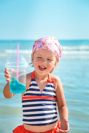 swimsuite: Happy little girl in swimsuit with blue cocktail on the beach. Summer. Vacation. Sea. Ocean