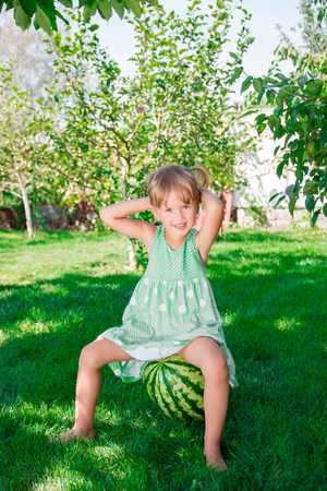 Little girl in green dress barefoot sitting on watermelon in the park. Summer time. HAppy. Joy