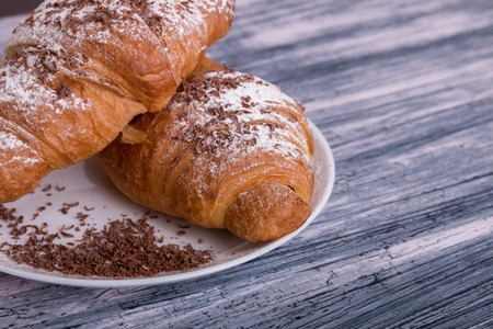 Croissants with powdered sugar and chocolate on white plate on colored wood background. Top view. Copy space Stock Photo