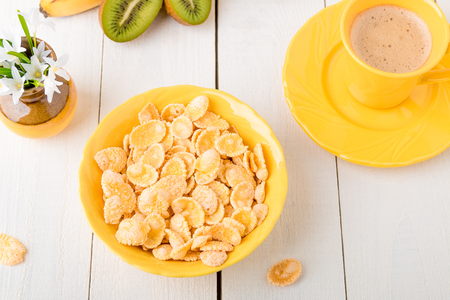 Healthy breakfast with cereal flakes and fruit near vase with flowers on white background. Yellow tone. Top view