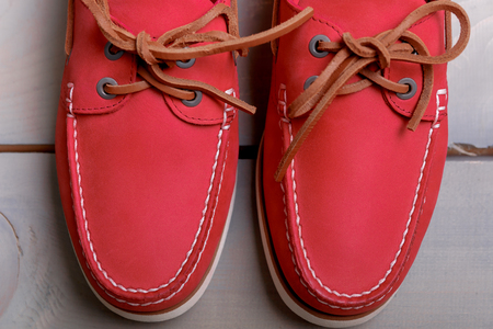 loafers: Red boat shoes on wooden background. Top view. Close up
