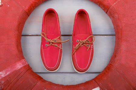 Red boat shoes on wooden background near lifebuoy. Top view. Close up