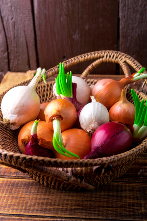 close up of onions in a basket: Different onions in basket on wooden background. Rustic style. Close up.