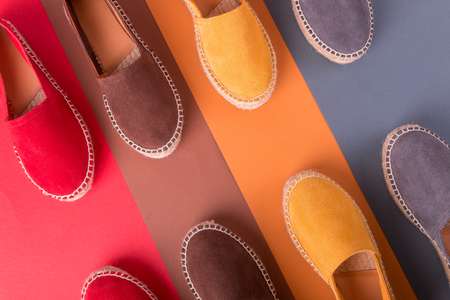Four pair of espadrilles on multicolor background. Top view