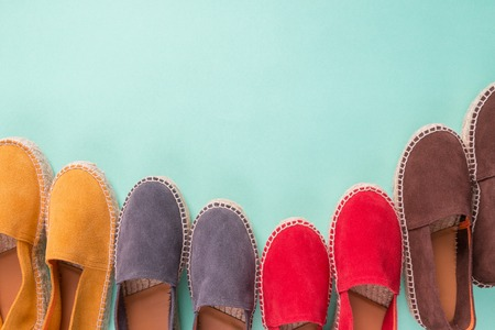 Four pair of espadrilles on mint color background. Top view. Copy space