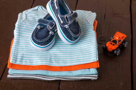 Folded blue and orange    bodysuit with boat shoes on it on  wooden background. diaper for newborn boy. Stack of infant clothing. Child outfit. Close up. Stock Photo
