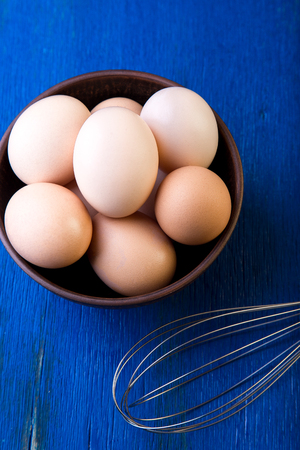 Fresh eggs in a brown bowl on  blue background. Top view.