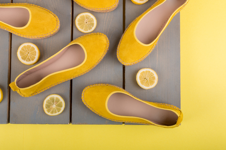 Yellow espadrilles shoes near slices of lemon on wooden background. Top view